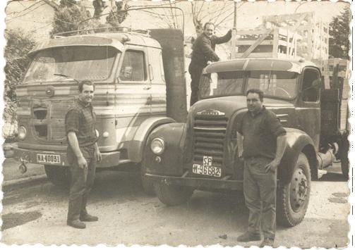 Foto antigua de dos camiones y trabajadores